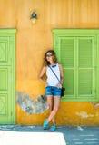 Junge blonde Frau in der typischen griechischen Stadt mit bunten Gebäuden auf Kastelorizo-Insel, Griechenland Lizenzfreie Stockbilder