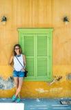 Junge blonde Frau in der typischen griechischen Stadt mit bunten Gebäuden auf Kastelorizo-Insel, Griechenland Stockbilder