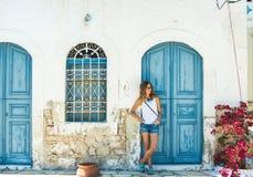 Junge blonde Frau an der typischen griechischen traditionellen Stadt mit bunten Gebäuden auf Kastelorizo-Insel, Griechenland Lizenzfreie Stockfotos