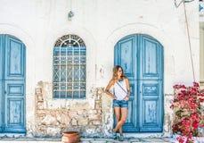Junge blonde Frau an der typischen griechischen traditionellen Stadt mit bunten Gebäuden auf Kastelorizo-Insel, Griechenland Stockbilder