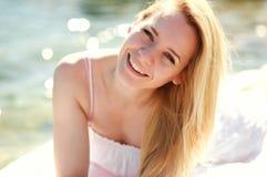 Junge blonde Frau des Nahaufnahmeporträts, die glücklich auf Seestrand stillsteht Stockbild