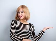 Junge blonde Frau des schönen Makes-up, die someth hält und darstellt Lizenzfreie Stockfotos