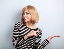 Junge blonde Frau des schönen Makes-up, die someth hält und darstellt Lizenzfreies Stockbild