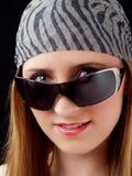 Junge blonde Frau, die über Sonnenbrillen späht Stockbilder