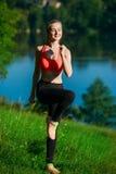 Junge blonde Frau, die Übungen in der Natur tut Ein Sportmädchen in einer roten Weste steht in einem Park nahe dem Fluss Stockbild