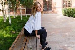 Junge blonde Frau, die auf Bank und hergestellten Bogenlippen stillsteht Stockfoto