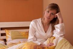 Junge blonde Frau, die auf Bett und dem Lächeln sitzt Stockbild