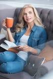 Junge blonde Frau, die auf Couch mit Buch und Schale sitzt Stockbilder