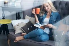 Junge blonde Frau, die auf Couch mit Buch und Schale sitzt Lizenzfreie Stockbilder