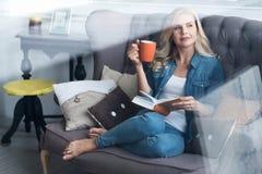 Junge blonde Frau, die auf Couch mit Buch und Schale sitzt Lizenzfreies Stockbild