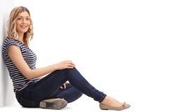 Junge blonde Frau, die auf dem Boden sitzt Stockbilder