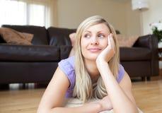 Junge blonde Frau, die auf dem Fußboden liegt Stockfoto