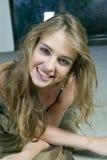 Junge blonde Frau, die auf dem Fußboden liegt Stockbild