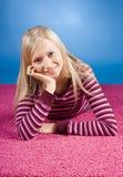 Junge blonde Frau, die auf dem rosafarbenen Teppich liegt Lizenzfreie Stockfotos