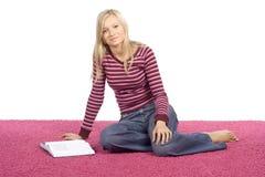 Junge blonde Frau, die auf dem rosafarbenen Teppich mit Buch sitzt Stockfotografie