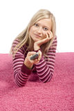 Junge blonde Frau, die auf dem rosafarbenen Teppich mit Fernsteuerungs liegt Lizenzfreie Stockbilder