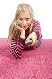 Junge blonde Frau, die auf dem rosafarbenen Teppich mit Fernsteuerungs liegt Stockbilder