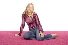 Junge blonde Frau, die auf dem rosafarbenen Teppich sitzt Lizenzfreie Stockfotos