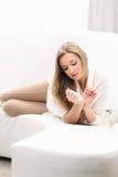 Junge blonde Frau, die auf dem Sofa liegt Lizenzfreie Stockfotos