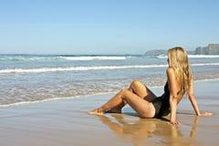 Junge blonde Frau, die auf dem Strand sich entspannt Stockbilder