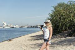 Junge blonde Frau, die auf dem Strand stillsteht Stockfotografie