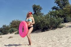 Junge blonde Frau, die auf dem Strand stillsteht Stockbilder