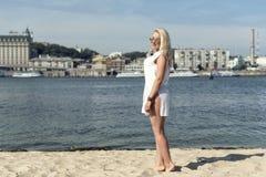 Junge blonde Frau, die auf dem Strand stillsteht Lizenzfreies Stockbild