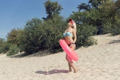 Junge blonde Frau, die auf dem Strand stillsteht Stockfoto
