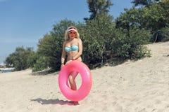 Junge blonde Frau, die auf dem Strand stillsteht Lizenzfreies Stockfoto