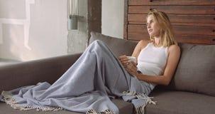Junge blonde Frau, die auf der Couch sich entspannt Lizenzfreies Stockbild