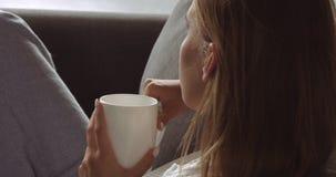 Junge blonde Frau, die auf der Couch sich entspannt Lizenzfreie Stockbilder