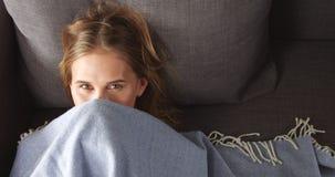 Junge blonde Frau, die auf der Couch sich entspannt Lizenzfreies Stockfoto