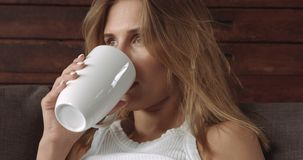 Junge blonde Frau, die auf der Couch sich entspannt Stockfoto
