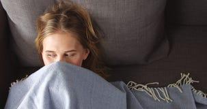 Junge blonde Frau, die auf der Couch sich entspannt Lizenzfreie Stockfotografie