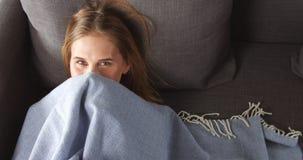 Junge blonde Frau, die auf der Couch sich entspannt Stockbild