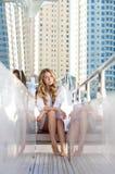 Junge blonde Frau, die auf der Yacht sitzt Stockbilder