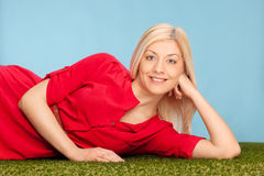Junge blonde Frau, die auf einem Feld liegt Lizenzfreie Stockbilder