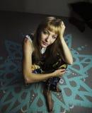 Junge blonde Frau, die auf einem gemalten Boden sitzt Stockbilder