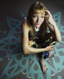 Junge blonde Frau, die auf einem gemalten Boden sitzt Stockfotografie