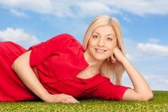 Junge blonde Frau, die auf einem Gras liegt Lizenzfreies Stockfoto