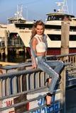 Junge blonde Frau, die auf einem Pier mit Schiff auf dem Hintergrund aufwirft Art und Weiseblick Lizenzfreie Stockbilder