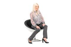 Junge blonde Frau, die auf einem Stuhl sitzt Lizenzfreies Stockbild