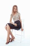 Junge blonde Frau, die auf einem Stuhl sitzt Lizenzfreie Stockfotos