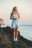 Junge blonde Frau, die auf Felsen durch das Meer steht Stockbilder