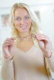 Junge blonde Frau, die auf Gläsern versucht Lizenzfreie Stockfotografie