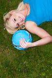Junge blonde Frau, die auf Gras liegt Lizenzfreie Stockfotos