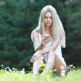 Junge blonde Frau, die auf Gras sitzt Lizenzfreies Stockfoto