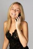 Junge blonde Frau, die auf Handy spricht Lizenzfreie Stockbilder
