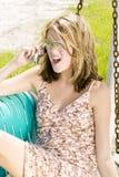 Junge blonde Frau, die auf ihrem Handy spricht Stockfoto