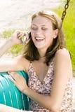 Junge blonde Frau, die auf ihrem Handy spricht Lizenzfreies Stockfoto